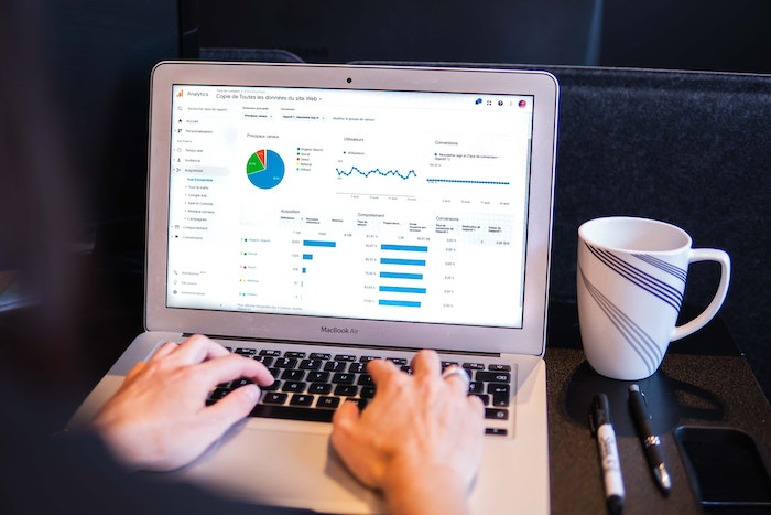 Google Ads process on laptop along with a mug and pens.
