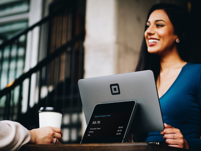 Woman smiling while using her laptop due to the increase of local SEO website traffic.