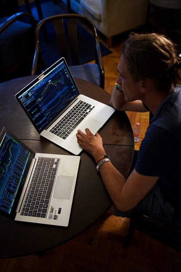 Man sitting and using 2 laptops for keyword research of a business.